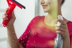 Kvinna som gör ren ett fönster fotografering för bildbyråer