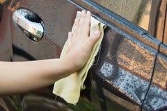 kvinna som gör ren hennes bil genom att använda microfibertorkduken Royaltyfria Bilder