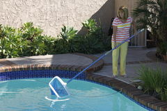 Kvinna som gör ren hennes simbassäng Arkivfoto