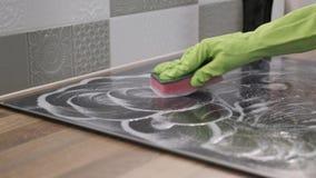 Kvinna som gör ren modern laga mat keramisk elektrisk yttersida för exponeringsglas lager videofilmer