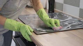 Kvinna som gör ren modern laga mat keramisk elektrisk yttersida för exponeringsglas stock video