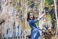 Kvinna som gör selfie i naturen, härlig flicka som fotograferas i parkera på din smartphone Royaltyfria Foton