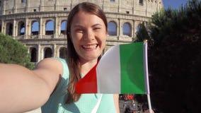 Kvinna som gör selfie nära Colosseum i Rome, Italien Tonårs- flicka som vinkar den italienska flaggan i ultrarapid stock video