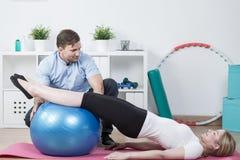 Kvinna som gör sjukgymnastikövningar arkivfoto