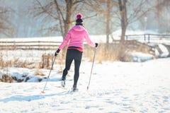 Kvinna som gör skidåkning för argt land som vintersport arkivbild