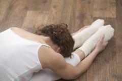 Kvinna som gör sträcka övning på ädelträgolv fotografering för bildbyråer