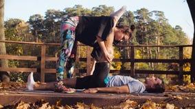 Kvinna som gör sträcka övningar för en man stock video