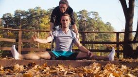 Kvinna som gör sträcka övningar för en man lager videofilmer