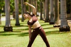 Kvinna som gör sträckning för sportar som utbildar på Morning-2 Royaltyfri Foto
