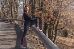 Kvinna som gör sträckning, innan att jogga i skog fotografering för bildbyråer