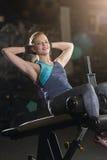 Kvinna som gör styrkaövningar för absmuskler Arkivfoton