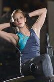 Kvinna som gör styrkaövningar för absmuskler Arkivfoto