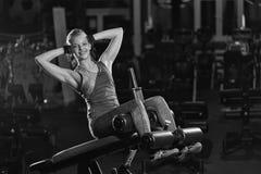 Kvinna som gör styrkaövningar för absmuskler Arkivbilder