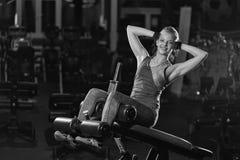 Kvinna som gör styrkaövningar för absmuskler Arkivbild