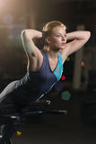 Kvinna som gör styrkaövningar för absmuskler Royaltyfria Bilder