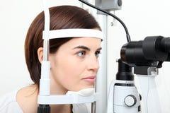 Kvinna som gör synförmågamätning med den optiska slitslampan royaltyfria foton