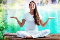 Kvinna som gör yogaövning på sjön Arkivfoto