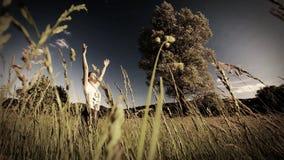 Kvinna som gör yoga i mitt av ett fält av högt gräs - gradera för sepiastil arkivfilmer