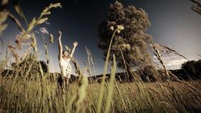 Kvinna som gör yoga i mitt av ett fält av högt gräs - gradera för sepiastil - ultrarapid arkivfilmer