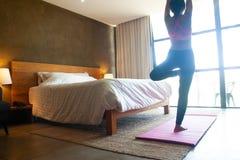Kvinna som gör yoga i sovrum sund livsstil för begrepp arkivbilder