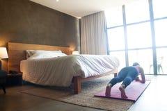 Kvinna som gör yoga i sovrum Sund livsstil royaltyfria bilder