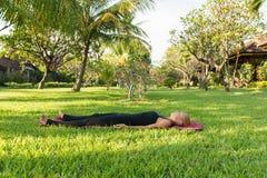 Kvinna som gör yoga i trädgård Fotografering för Bildbyråer