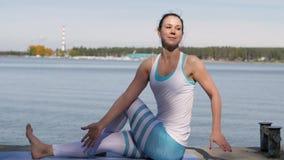 Kvinna som gör yoga nära vattnet på pir Yoga i natur stock video