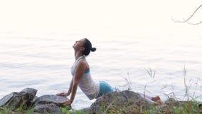 Kvinna som gör yoga nära vattnet på pir Yoga i natur lager videofilmer