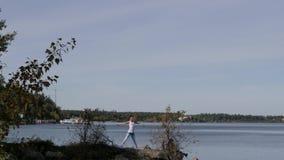 Kvinna som gör yoga nära vattnet på pir Yoga i natur arkivfilmer