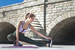 Kvinna som gör yoga, och pilates som är utomhus- med henne som är matt Arkivbilder