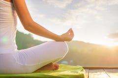 Kvinna som gör yoga på kusten - halvt diagram sammanträde royaltyfri foto
