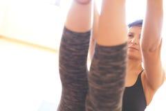 Kvinna som gör yoga på trägolvet royaltyfria bilder