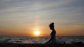 Kvinna som gör yoga vid havet Kvinnlig silhouette Kundalini yoga arkivfilmer
