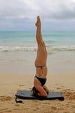 Kvinna som gör yogahuvudstående på stranden Royaltyfri Bild