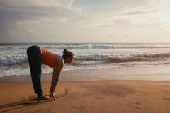 Kvinna som gör yogasolhälsningen Surya Namaskar på stranden royaltyfri bild