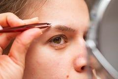 Kvinna som g?r hennes eyebows arkivbilder