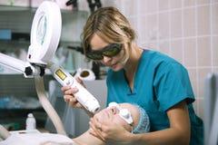 Kvinna som genomgår laser-hudbehandling Arkivfoton