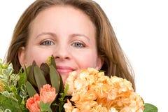 Kvinna som genuint in ser till dina ögon bak blomman Bouque Royaltyfri Foto