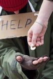 Kvinna som ger ett mynt till den hemlösa mannen royaltyfria foton