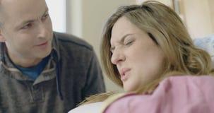 Kvinna som ger födelse med hennes make av hennes sida som stöttar henne