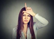 Kvinna som ger förloraretecknet som ser dig med avsmak på framsida royaltyfri foto