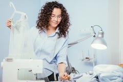 Kvinna som ger fulländande handlag av danandeklänningen på designstudion Arkivfoto