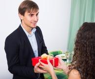 Kvinna som ger gåva till mannen Royaltyfri Foto