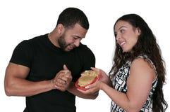 Kvinna som ger hamburgaren till en man royaltyfria bilder