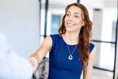 Kvinna som ger handskakningen efter överenskommelse Arkivfoton