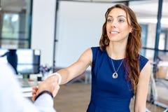 Kvinna som ger handskakningen efter överenskommelse Fotografering för Bildbyråer