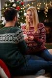 Kvinna som ger julgåva till mannen royaltyfri bild