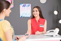 Kvinna som ger kreditkorten till receptionisten på skrivbordet arkivfoto