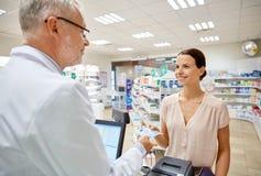 Kvinna som ger pengar till apotekaren på apoteket royaltyfria foton