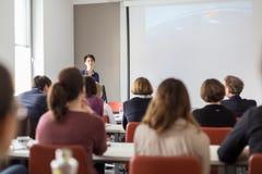 Kvinna som ger presentation i hörsal på universitetet royaltyfri bild